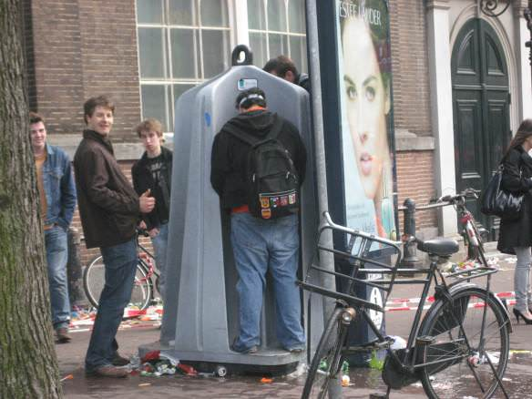 several guys peeing at a 4 person Amsterdam outdoor urinal as one guy gives a thumbs up