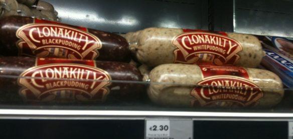 Clonakilty black and white Irish pudding on grocery store shelf.