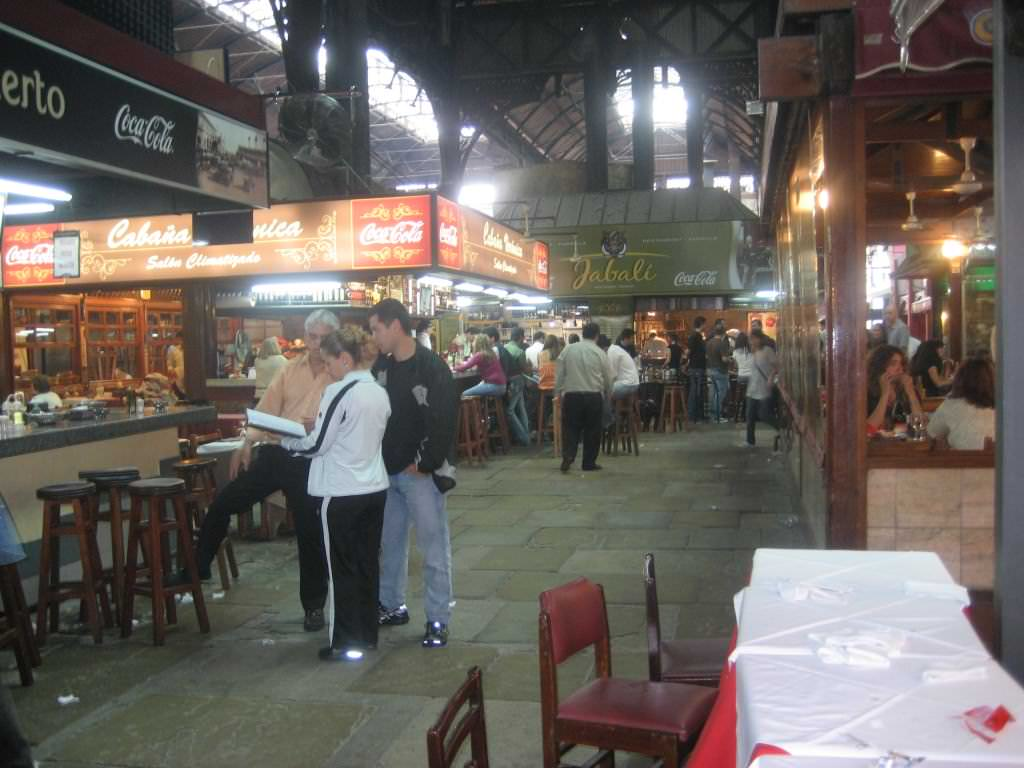 Montevideo, Uruguay's Mercado del Puerto (meat market) famous for fantastic and cheap fast food steak meals at every turn. Flights to Montevideo are limited but a ferry connects the Uruguay capital with Buenos Aires, Argentina which has more flight options. how to book the cheapest flight