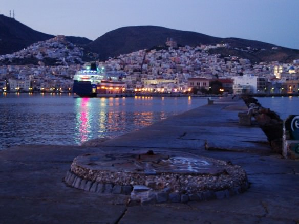 View of Syros from the end of the pier at twilight with a ferry docked
