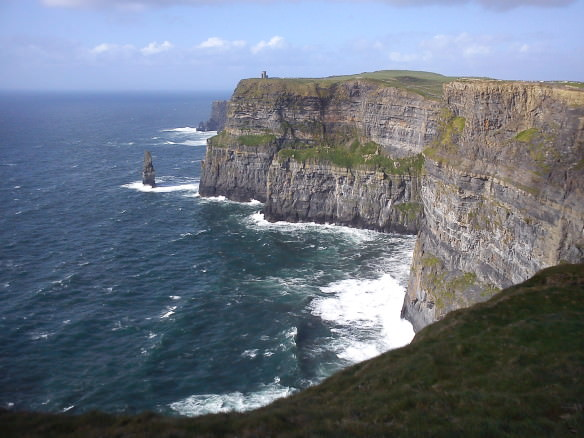 Cliffs of Moher in County Clare with sea and waves and castle off in the distance