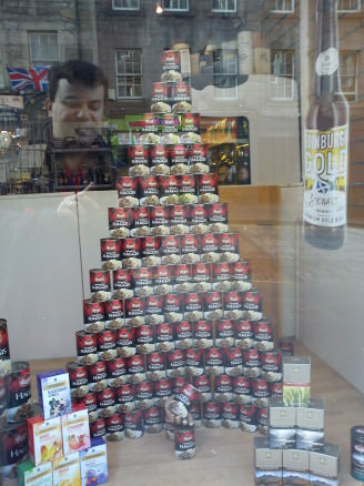 A pyramid of canned haggis in a Royal Mile shop, with the ghost of Haggis lover's past lurking. Haggis and whisky feast!