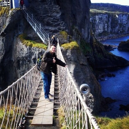 Alex walking in the middle of the Carrick-a-Rede rope bridge in Northern Ireland