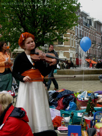 Girl playing violin o the street for Queensday