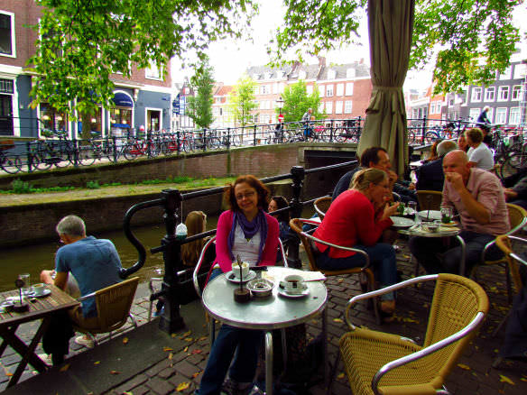 Bell sitting having coffee beside a canal in Amsterdam