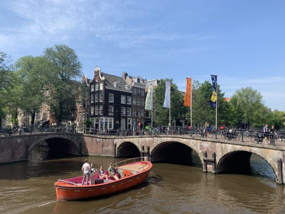 A small red boat about to pass under an arched bridge on the canal in Amsterdam