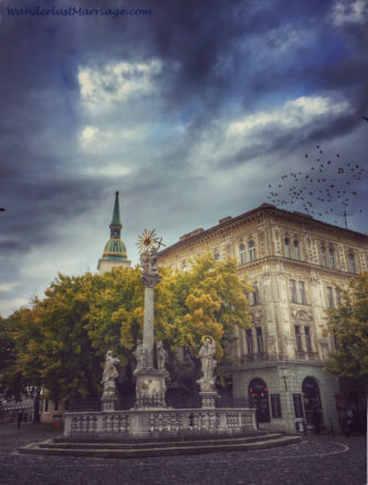 Statue in the square with birds in the storm sky