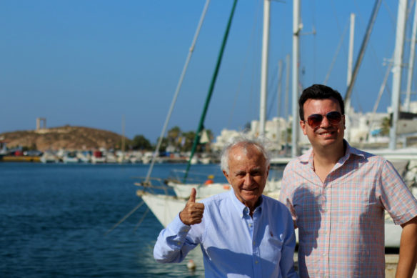 Alex and his dad at the Naxos harbor and boats in the background