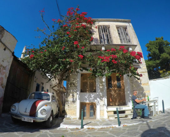 House with bright red flowers, blue sky and a VW betel car