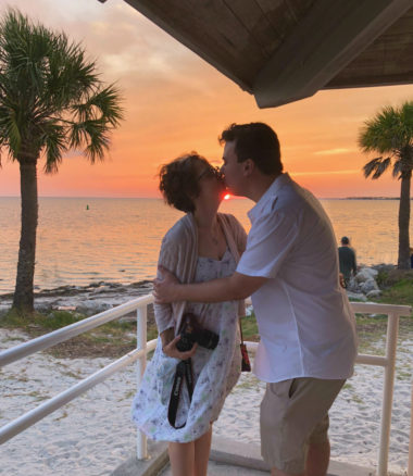 Alex and Bell kissing with sunset in the background on the aptly named Sunset Beach in Tarpon Springs, Florida