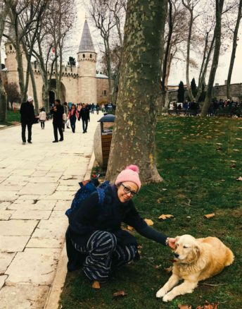 Bell petting a golden retriever dog out the front of Topkapi