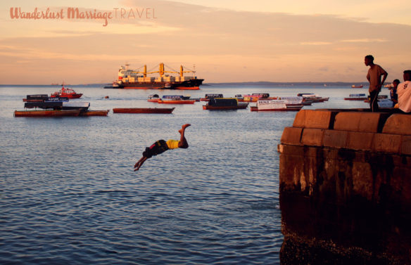 Kids diving off the sea wall into the ocean at sunset