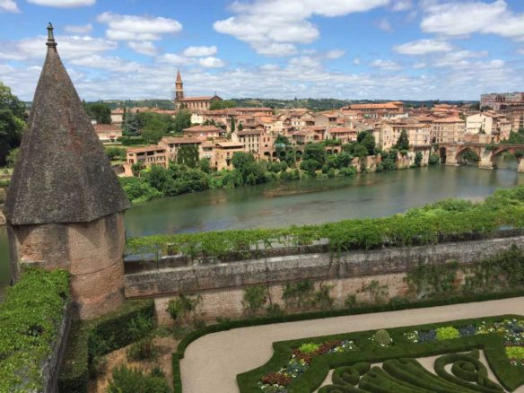River running through Albi withe blue skies and fluffy clouds