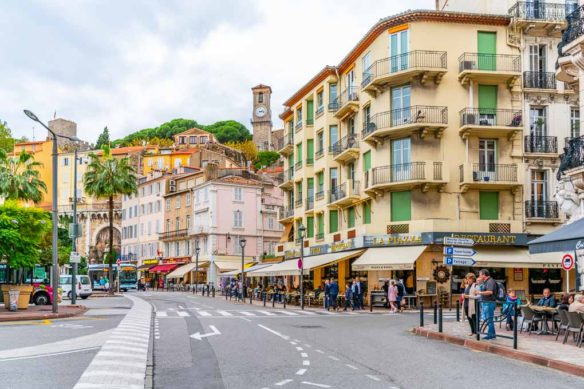 Street in Cannes with people walking and sitting at cafes