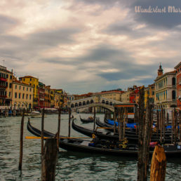 Canals with the gondolas parked and a dark moody sky over Venice