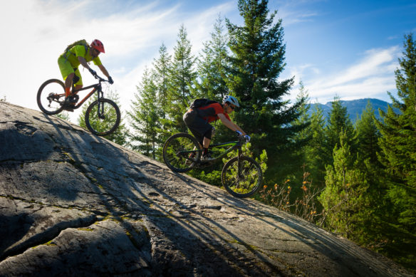 2 people mountain biking on a large rock