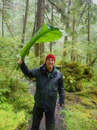 ALex hiking and using a large leaf as an umbrella