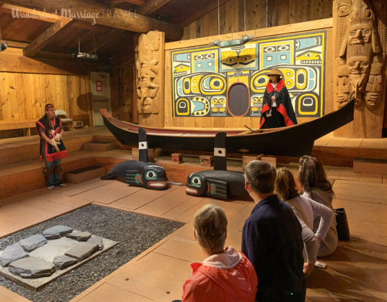 Member of the Tlingit tribe telling their story in the cedar wood tribal house