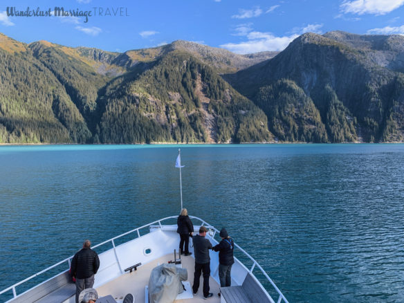Front of boat, clean blue water and fjords under a blue sky in Alaska