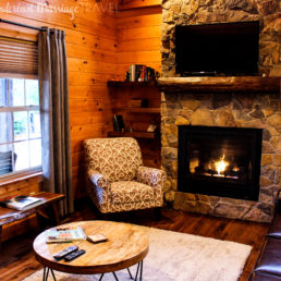 Cabin room with fire and comfy chairs