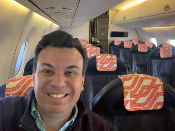Alex with the seats on the plane behind him empty