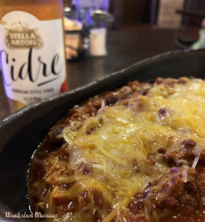 Bowl of chili topped with cheese and a beer