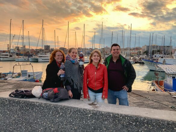 four travel bloggers drinking wine on the port of Catania