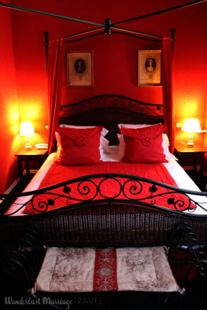 Four poster bed with red walls and red bed spread