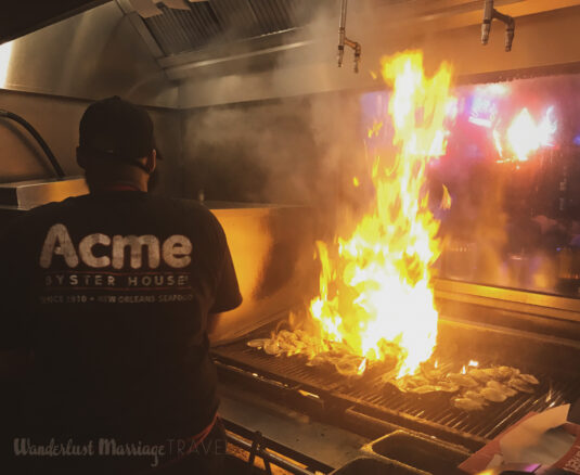 Chef flame grilling oysters at Acme oyster house