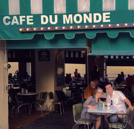 Alex and Bell sitting under the Cafe Du Monde awning