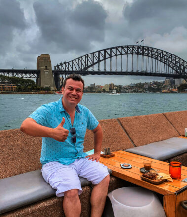 Alex giving a thumbs up to the Sydney harbor bridge