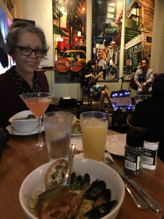 Bell at a table with drinks and mussels with art and musicians behind her