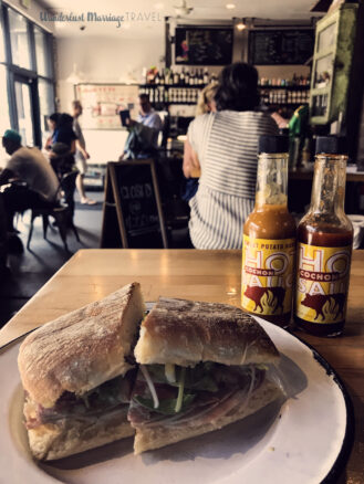 Muffaletta on a plate, with bottles of hot sauce and cafe in the background