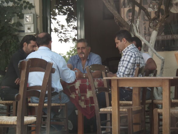 Greek men playing cards and smoking around a table on the Greek island of Aegina