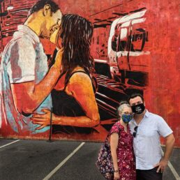 Alex & Bell with masks in front of a mural a guy kissing a girl
