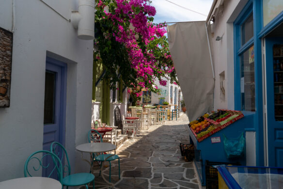 a small ally in town in Kythnos, Greece, with purple flowers hanging above aqua colored chairs alongside white buildings