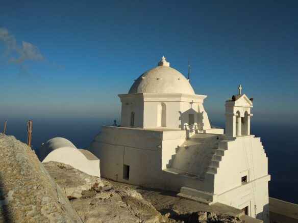 a small white church perched atop the mountain overlooking the Aegean Sea on the Greek Cyclades island of Anafi