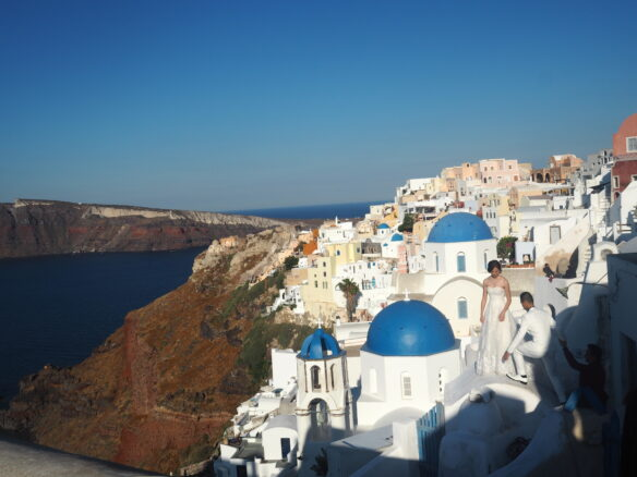 view of the cliffside town of Oia in Santorini, Greece, with buildings built into the cliffs, with the Aegean Sea in the backdrop