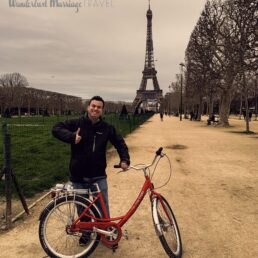 Alex with a red bike and giving a thumbs up in front of the Eiffel Tower