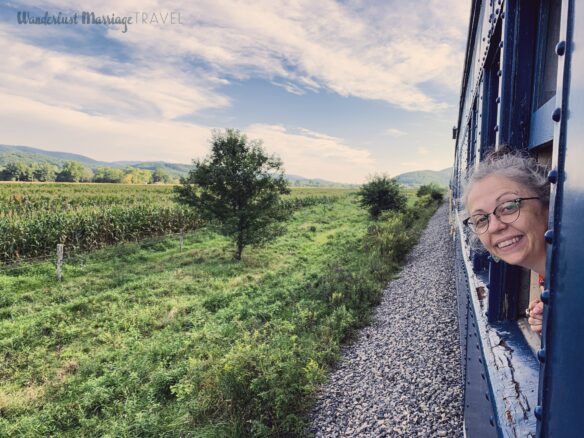 Bell with her head stuck out of the train carriage window with mountains and blues skies