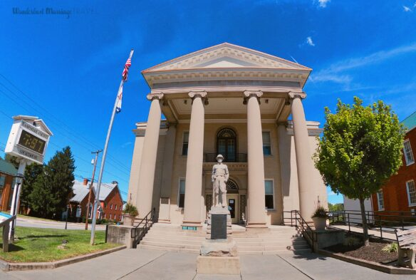 Courthouse with four Greek columns and a war statue, next to the court house is the American flag and a tree with blue skies