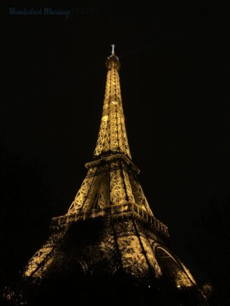 Tall metal structure lit up in golden lights at night