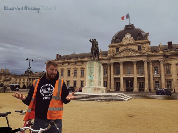 Tour guide talking out the front of a large building with a statue of a guy on a horse