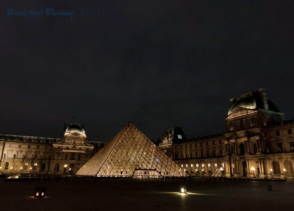 A glass pyramid lit up at night at the Louvre art museum