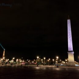 a large obelisk lit up at night, street lights, people walking around and the Eiffel Tower in the background at Place de la Concorde