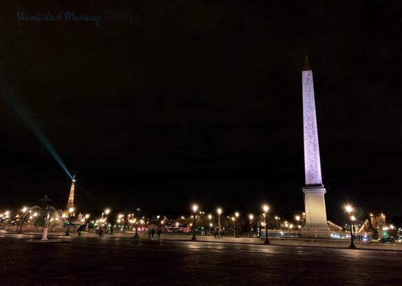 a large obelisk lit up at night, street lights, people walking around and the Eiffel Tower in the background