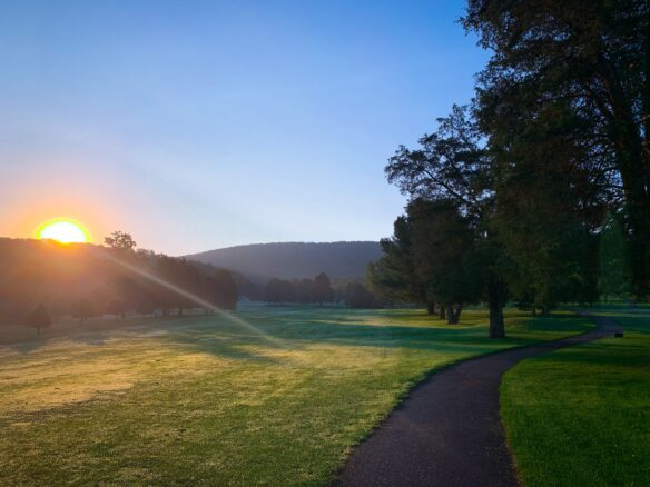 Sun rising over the mountains from the fairway of a golf course