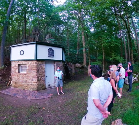 a little brick building where the spring water is collected and a tour group listening to the history of the water