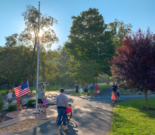 American flag being held by a small boy on the pole, with guest watching with the sun in the background with green trees