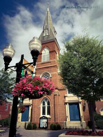 Picture of a red brick church with a lamp post and flower basket filled with pink flowers